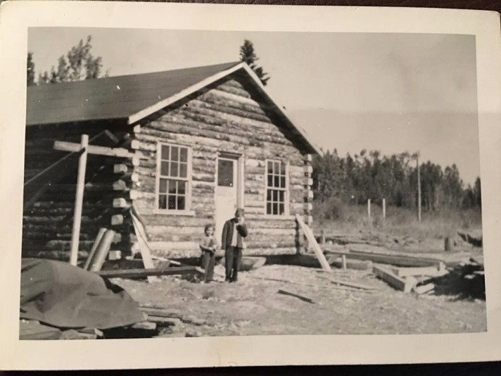 David and his sister Paula posing by cabin along the ALCAN highway in 1945.